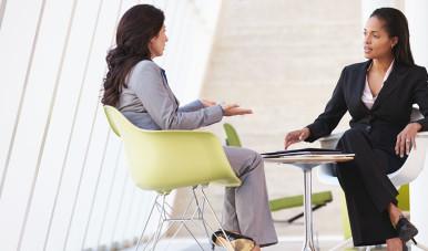 Na imagem, duas moças conversam em um escritório.