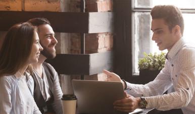 Na imagem, jovem vendedor apresenta discurso de vendas para casal.