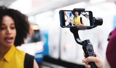 Na imagem, vemos uma pessoa gravando, pelo celular, um vídeo que será postado nas redes sociais