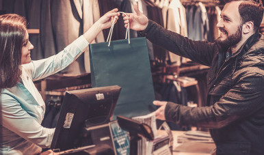 Vendedor oferece um produto a uma cliente em loja de roupas.
