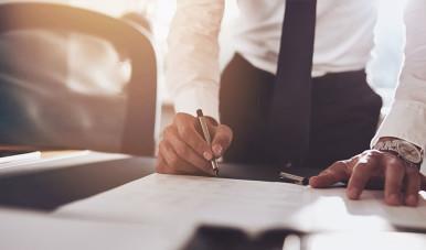 Na imagem, vemos uma pessoa assinando um contrato e firmando uma sociedade.