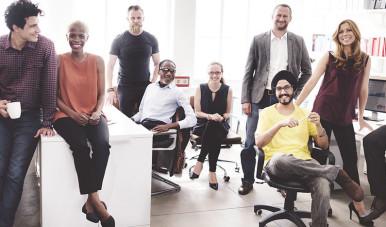 Imagem de grupo de pessoas, de diversas nacionalidade, de uma startup reunidos.