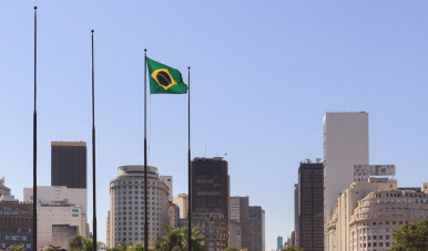 Na imagem, vemos a cidade de São Paulo rodeada de prédios e da bandeira do Brasil