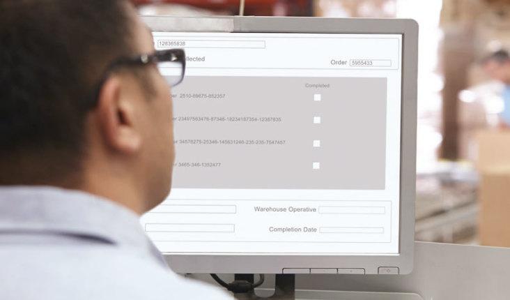 Profissional de controle de estoque mexendo em software