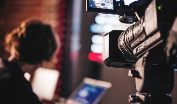 Na imagem, vemos uma câmera filmando algumas pessoas utilizando computadores.